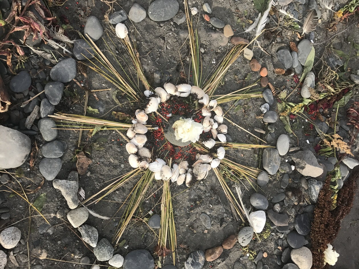 Circular nature art on the ground made form stones and plant materials
