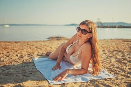 Woman in White Bikini Lying on Beach Sand