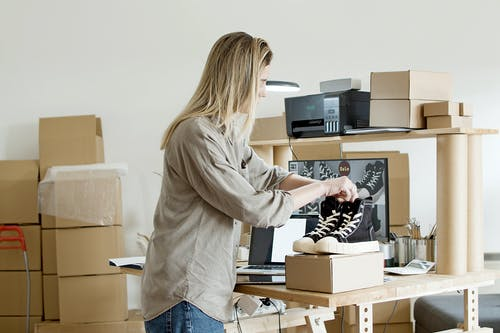 Woman Holding Black Shoes on Top of the Box