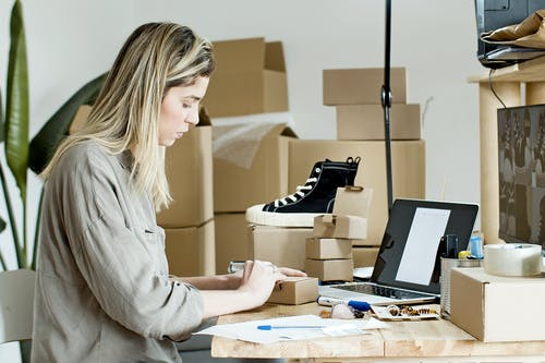 Woman Using Brown Box for Packaging