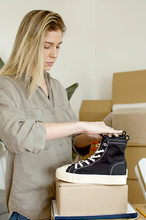 Woman Fixing the Black Shoes on Top of the Box