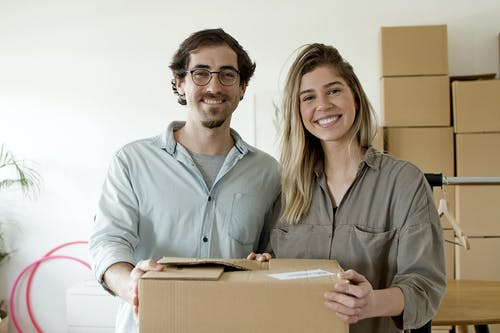 Couple Smiling while Holding the Package