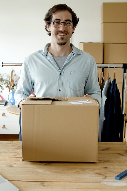Man Smiling while Holding the Package