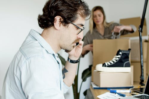 Man on the Phone while Woman Busy Packing