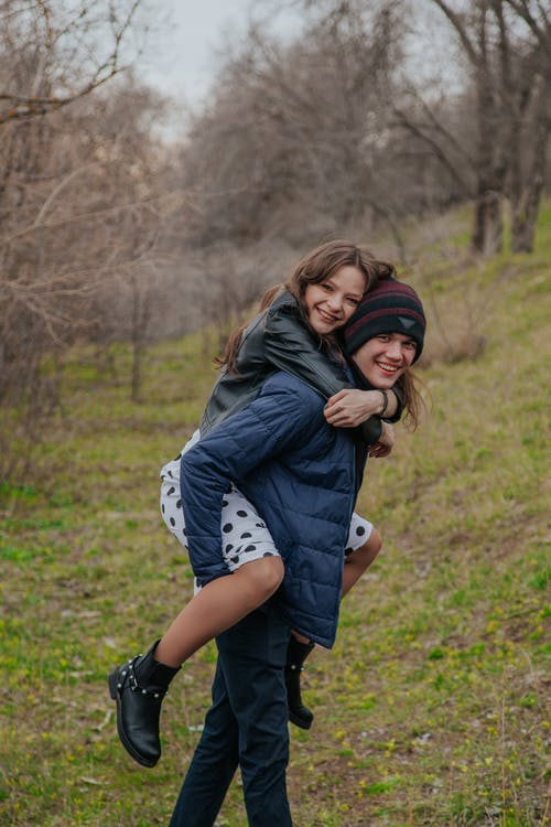 Cheerful boyfriend giving piggyback ride to girlfriend and looking at camera while standing on grassy ground near trees in countryside