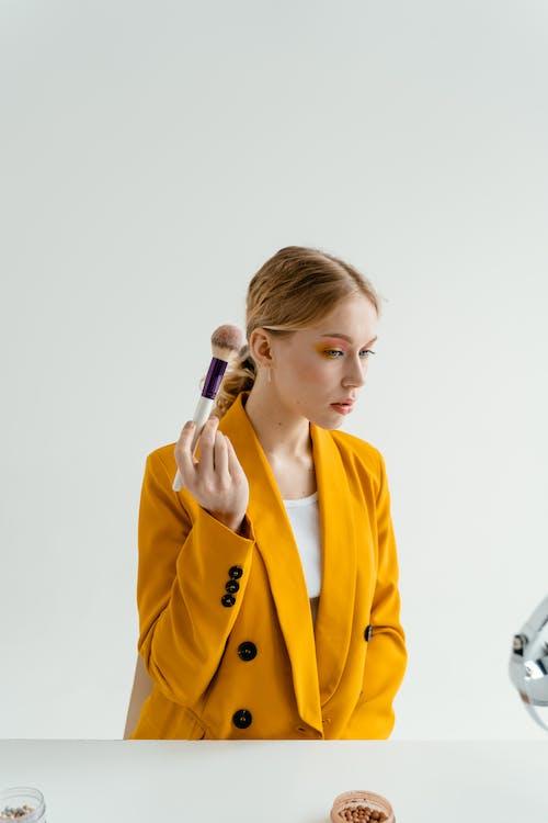 Woman in Yellow Coat Holding Makeup Brush