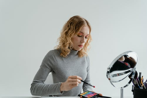 Woman in Gray Long Sleeve Shirt Holding a Makeup Palette