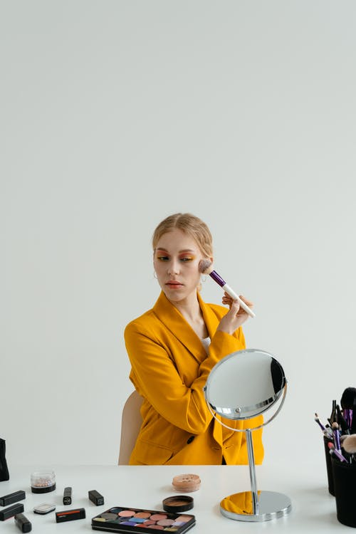 Woman in Yellow Blazer Applying Makeup