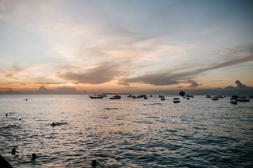 Silhouettes of faceless people swimming in ocean near boats under cloudy blue sky at sundown