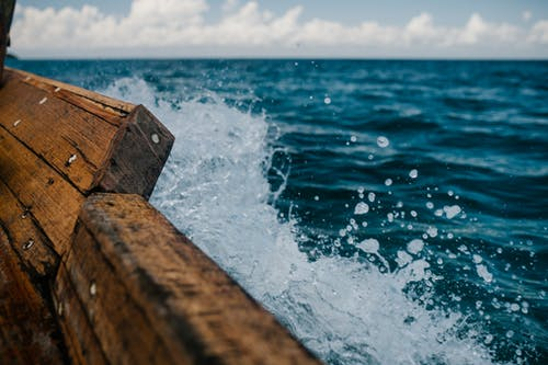 Detail of shabby wooden boat sailing in blue sea and splashing water in summer