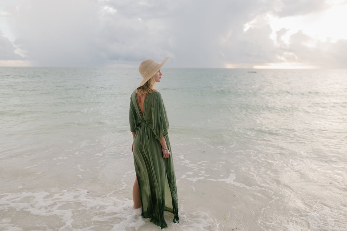 Back view of graceful female in maxi dress and straw hat standing in sea and looking away