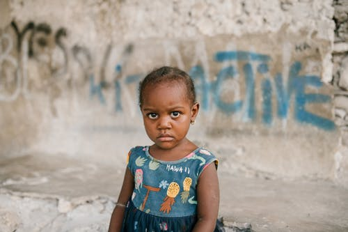 Frowning African American girl near weathered concrete building with vandal graffiti and broken wall in poor district