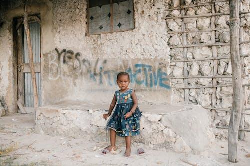 Little black girl sitting on rough stone border in ghetto