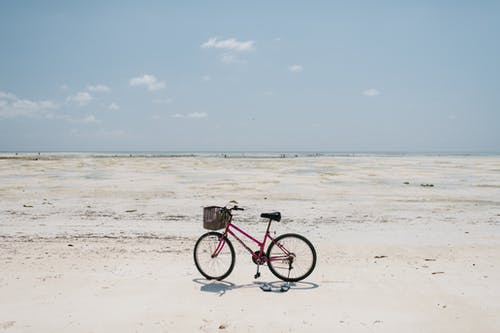 Bicycle parked on vast sandy shore of endless sea
