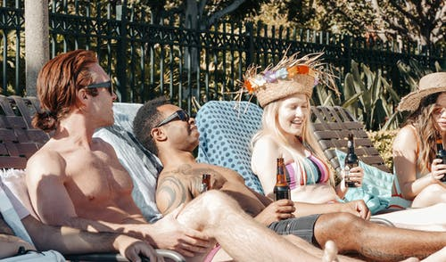 People Chilling and Relaxing while Holding Beer Bottles
