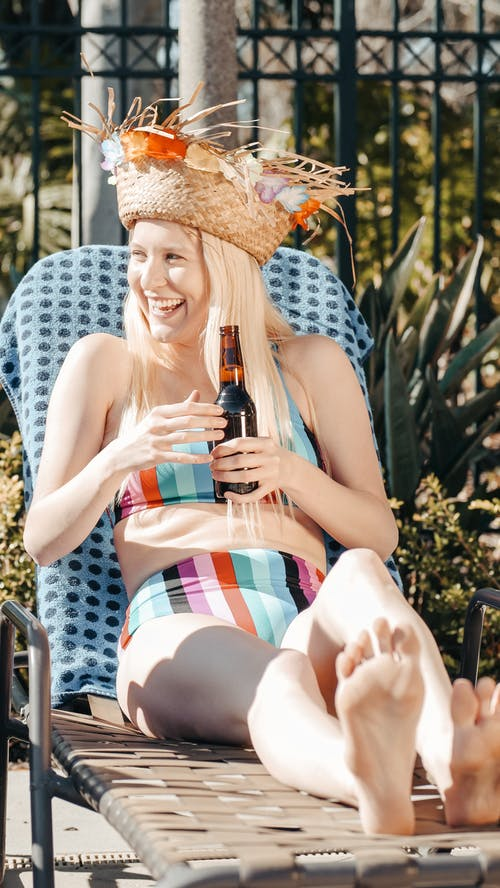 Woman in Bikini Smiling while Holding Beer Bottle