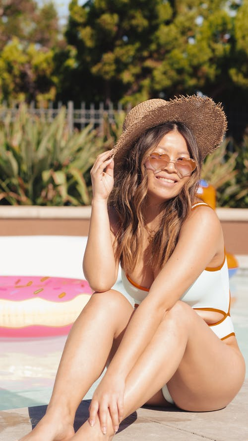 Woman Smiling while Sitting on the Poolside