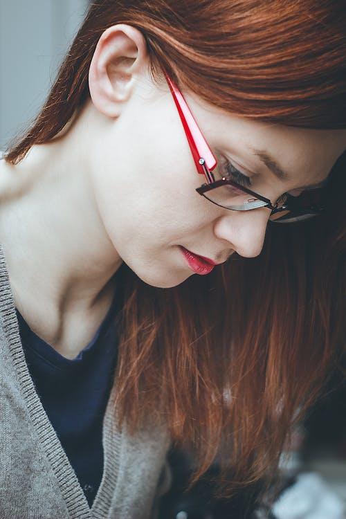 Woman Looking Down Wearing Red Eyeglasses