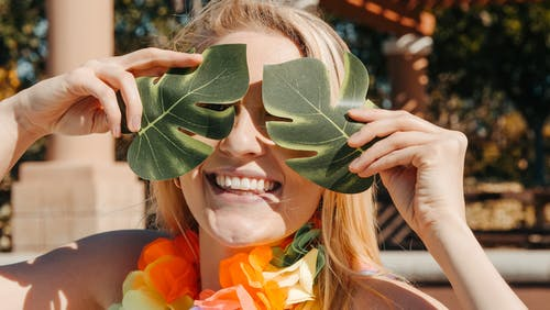 Woman Smiling while Covering Her Face with Two Leaves