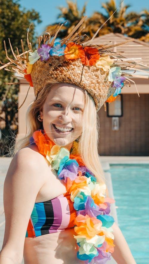 Woman in Bikini Smiling while Sitting on the Poolside