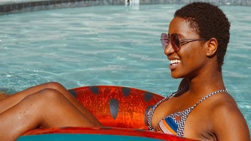 Woman Smiling while Swimming in the Pool