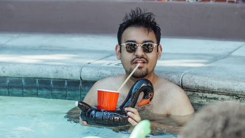 Man Swimming in the Pool while Drinking from the Plastic Cup