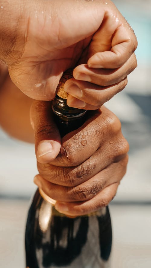 Close-Up Photo of Person Opening a Champagne Bottle