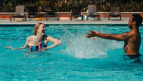 Man and Woman Having Fun Splashing Water to Each Other