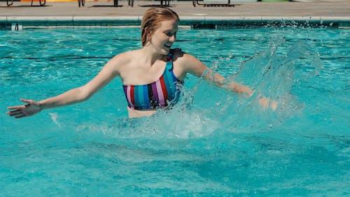 Woman Having Fun Splashing Water in the Swimming Pool
