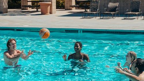 People Having Fun Playing Basketball in the Swimming Pool