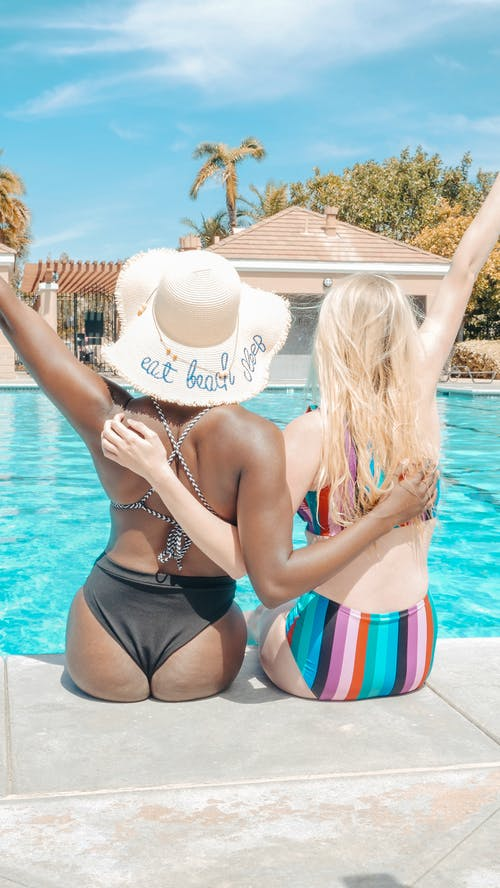 Back View of Women Sitting on Poolside