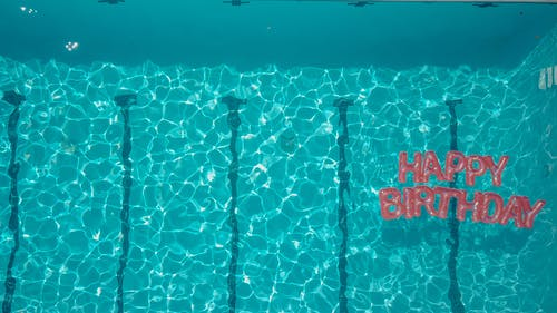 Top View of Happy Birthday Balloon Text in the Swimming Pool