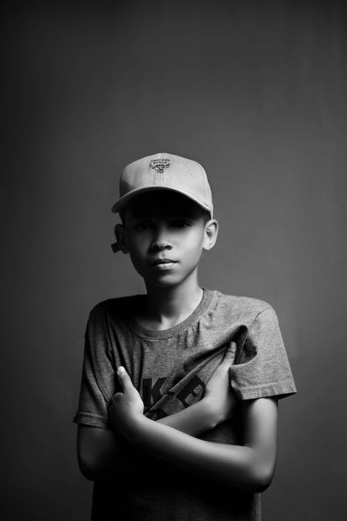 Grayscale Photo of Boy in Crew Neck T-shirt and Cap
