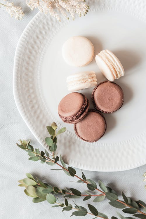 Top view arrangement of tasty macaroons of chocolate and vanilla flavors served on ceramic plate on white table