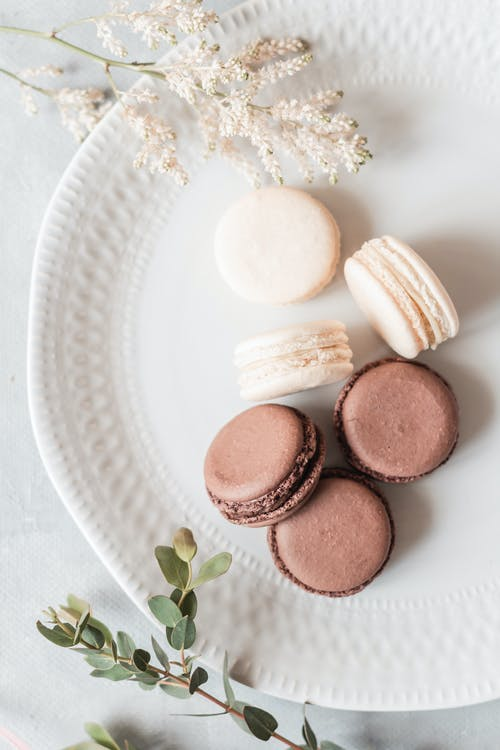 Overhead composition of delicious fresh macaroons of chocolate and vanilla flavors served on ceramic plate on plate