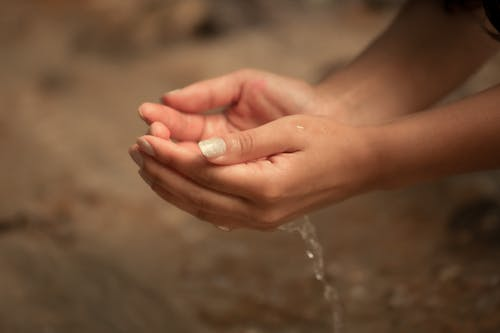 Crop anonymous female washing hands with clean transparent water on blurred background of nature