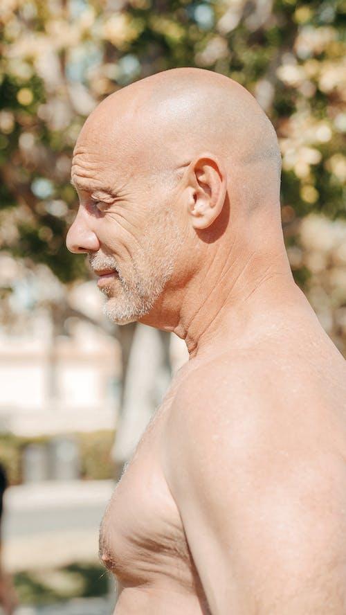 A Close-Up Shot of a Topless Man