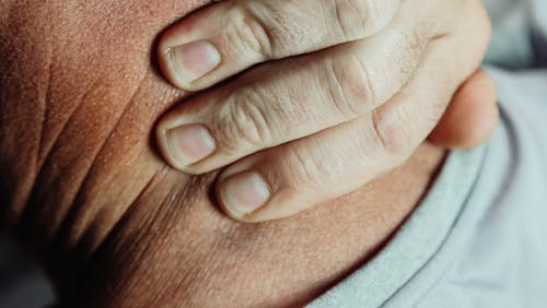 Close-Up Photo of a Person Having a Neck Pain
