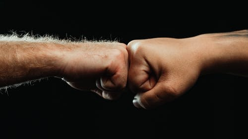 Close-Up of Two People Fist Bumping Each Other