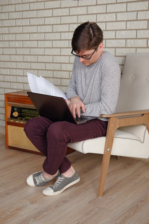 A Man Sitting on an Armchair while Using His Laptop