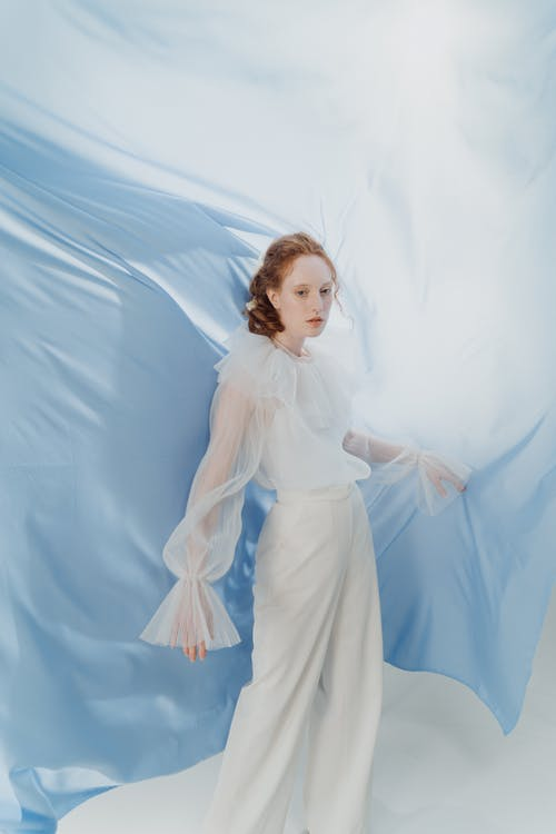 Girl in White Dress Standing on Blue Textile