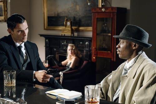 Man in Black Suit Jacket and Black Hat Sitting Beside Woman in Black Dress