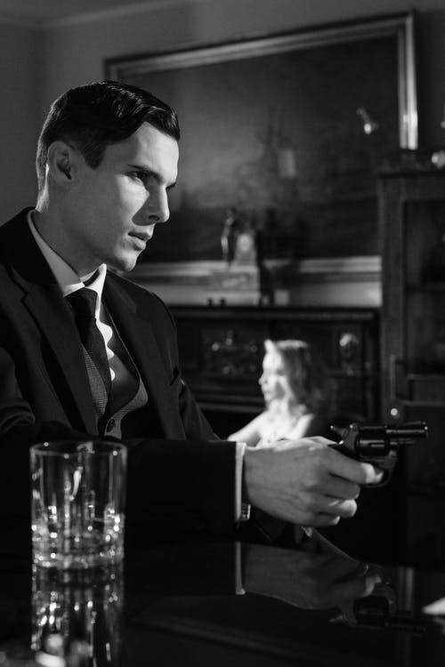 Man in Black Suit Holding Black Semi Automatic Pistol