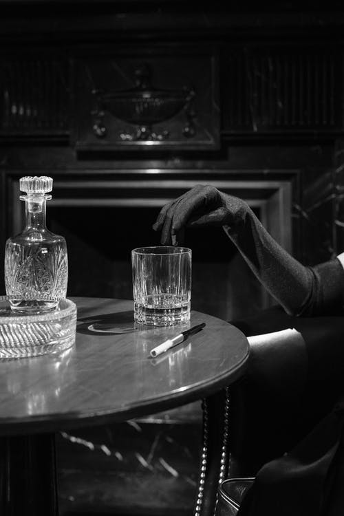 Monochrome Photo of Woman's Fingers on the Edge of Drinking Glass