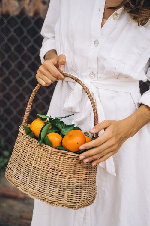 Person Holding Brown Woven Basket With Orange Fruits
