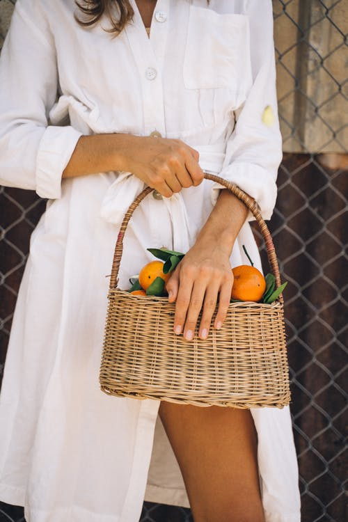 Woman in White Dress Shirt Holding Brown Woven Basket
