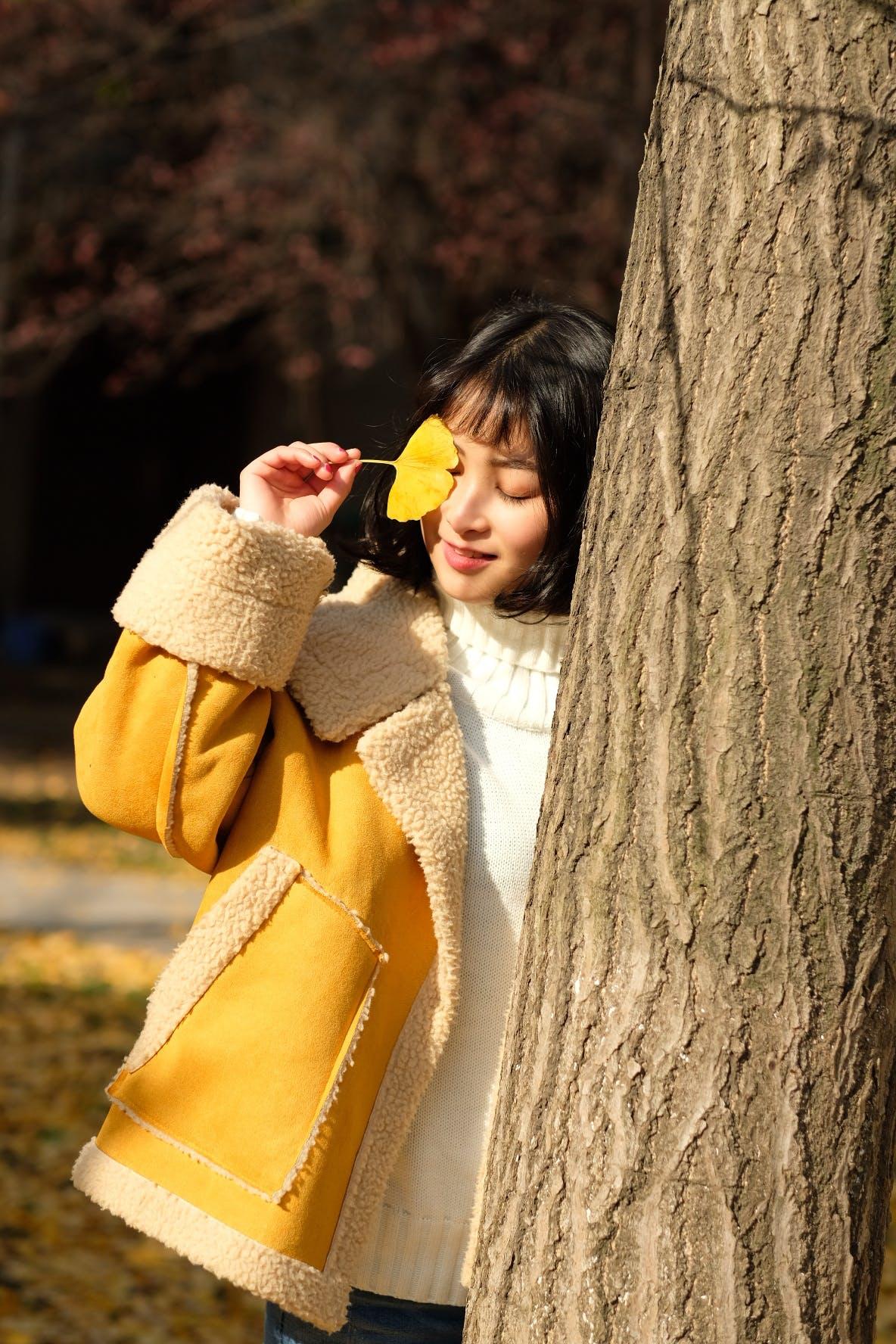 Woman Wearing Yellow Jacket Holding Yellow Leaf