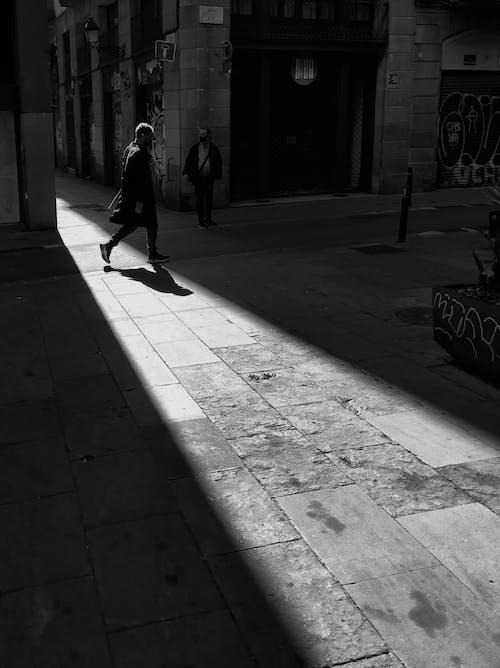 Grayscale Photo of Man Walking on Sidewalk