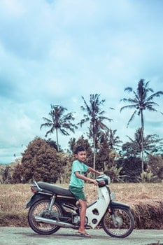 Boy Riding on White and Red Underbone Motorcycle