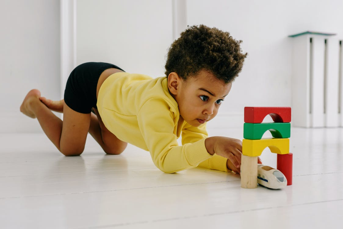 Boy in Yellow and White Striped Long Sleeve Shirt Playing With Lego Blocks